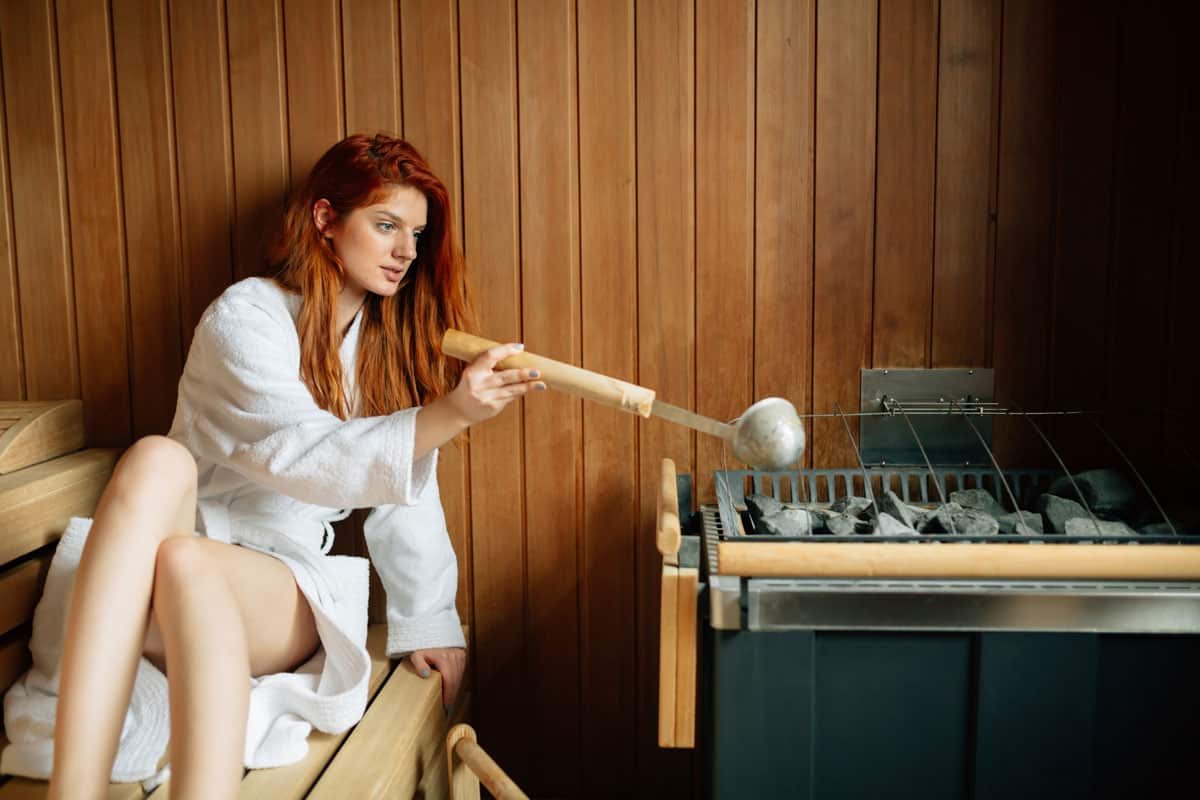 Girl pouring essential oils on hot stones in sauna